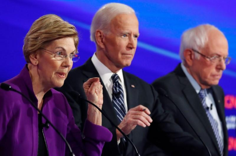 Democratic 2020 U.S. presidential candidates Senator Elizabeth Warren speaks with former Vice President Joe Biden and Senator Bernie Sanders listening at the seventh Democratic 2020 presidential debate at Drake University in Des Moines
