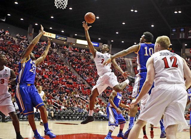 San Diego State guard Xavier Thames, center, shoots in front of the McNeese State defense during the first half of an NCAA college basketball game in San Diego, Saturday, Dec. 21, 2013. (AP Photo/Lenny Ignelzi)