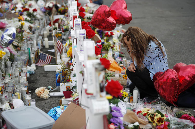 Gloria Garces kneels in front of crosses at a makeshift memorial near the scene of a mass shooting at a shopping complex in El Paso, Texas. (Photo: John Locher/AP)