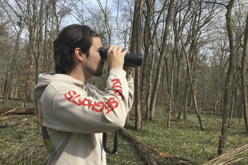 In this March 24, 2020 photo, provided by Conner Brown, he is seen using binoculars to look for birds in Cedar Island, Maryland. Brown, a 25-year-old law school student and Bitcoin aficionado, spent the early days of his coronavirus quarantine following his brother around on long walks as he hunted down and collected characters in a virtual reality video game called Pokemon Go.  (Elizabeth Wright/Courtesy of Conner Brown via AP)
