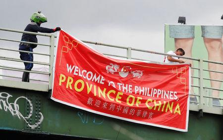 "Traffic enforcers remove a banner reading ""Welcome to the Philippines, Province of China"" hanging on an overpass along the C5 road intersection in Taguig, Metro Manila, Philippines July 12, 2018. REUTERS/Erik De Castro"