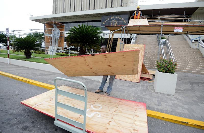 Workmen put up plywood on the Bank of Jamaica building to prepare it for the arrival of Hurricane Matthew, in Kingston, on October 1, 2016 (AFP Photo/Ricardo Makyn)
