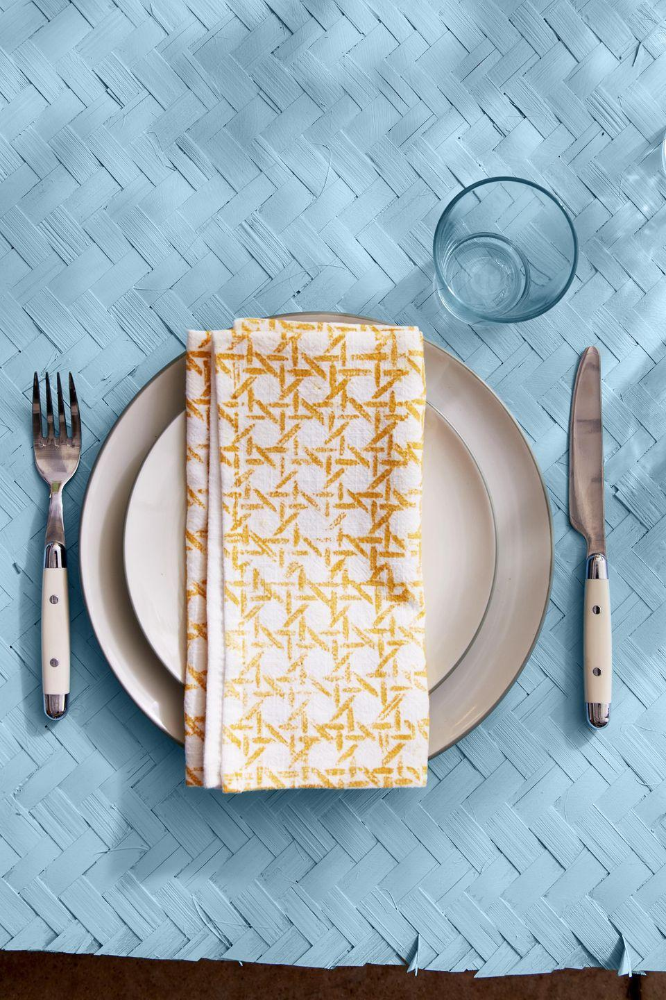 <p>Nothing classes up dinner like a cloth napkin and these DIY stamped ones transform plain white napkins into a real treat.<br><strong><br>To make:</strong> Create a stamp by cutting out a four-inch square of caning. Brush fabric paint on the front side of the caning, and press caning on an off-white linen napkin. Repeat, lining up the pattern as best you can, until one side of a napkin is fully covered.</p>