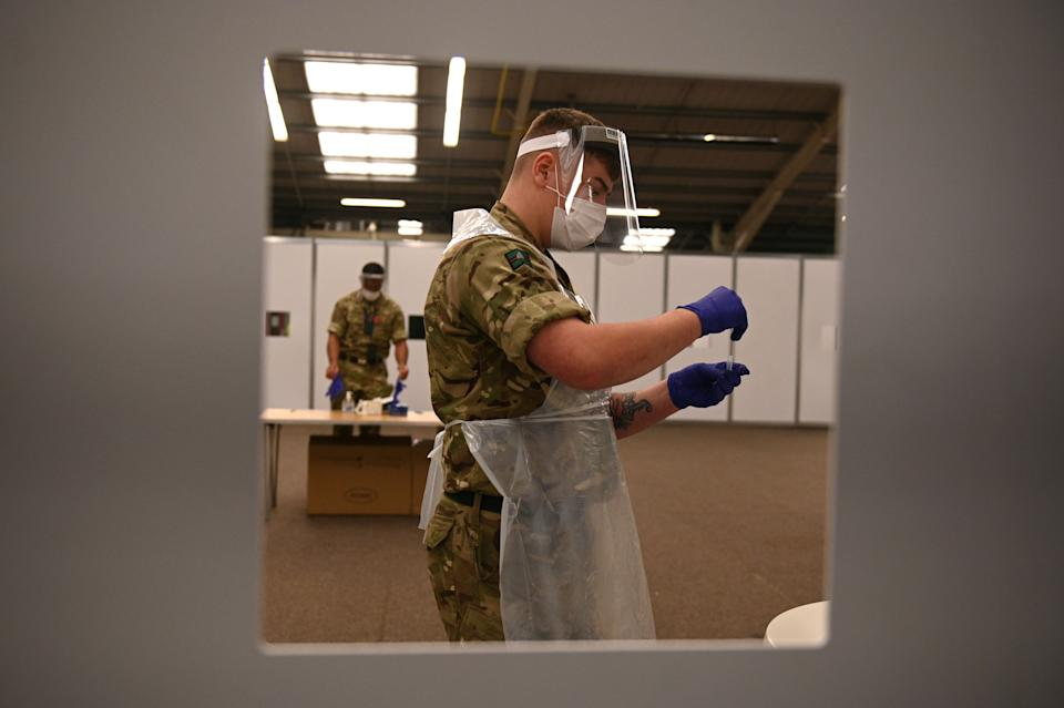 Soldiers wearing full PPE (personal protective equipment) process swabs from colleagues as they prepare for the arrival of members of the public inside the mass and rapid testing centre for the novel coronavirus COVID-19 at a Tennis centre in Liverpool on November 6, 2020. - To avoid extending the lockdown, Johnson is pinning his hopes on an ambitious new programme of Covid testing to detect and isolate infected people, starting with a city-wide trial launching in Liverpool today. (Photo by Oli SCARFF / AFP) (Photo by OLI SCARFF/AFP via Getty Images)