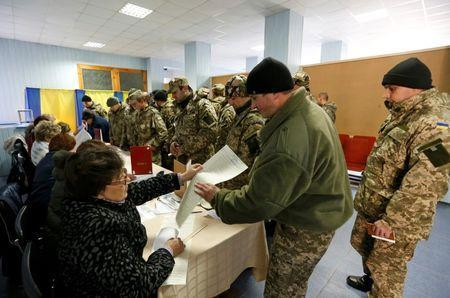 Members of Ukrainian government forces, who are taking part in a military operation in eastern Ukraine, visit a polling station during a parliamentary election in the town of Kramatorsk, October 26, 2014. REUTERS/Vasily Fedosenko