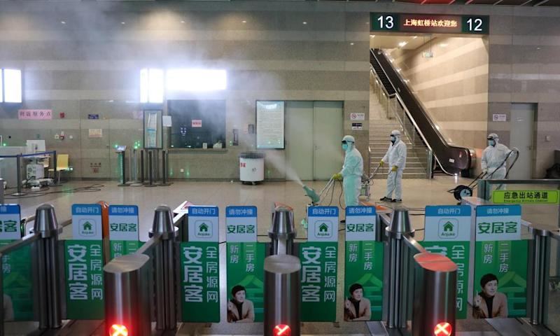 Workers in protective suits disinfect the Shanghai Hongqiao Railway Station