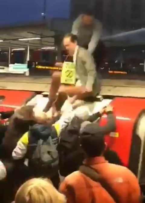 Commuters drag Mark Ovland down down from the roof of the train