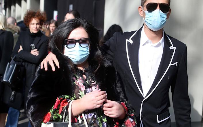 Guests wear face masks to protect against coronavirus upon arrival to attend the Dolce and Gabbana show during the Milan Fashion Week - Rex