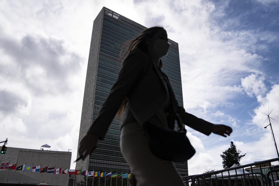 A pedestrian passes along police barricades surrounding the United Nations headquarters, Wednesday, Sept. 22, 2021, during the 76th Session of the U.N. General Assembly in New York. (AP Photo/John Minchillo)