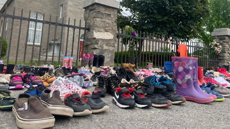 <p>Children's shoes were placed in front of a church in Kahnawake, in memory of the 215 children whose remains were found in a mass grave at a residential school in Kamloops, British Columbia. (Chloe Ranaldi/CBC)</p>