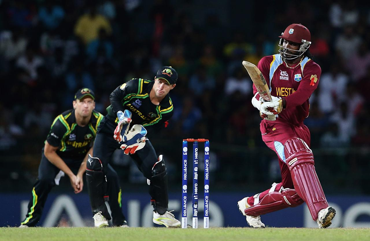 COLOMBO, SRI LANKA - OCTOBER 05:  Chris Gayle of the West Indies hits the ball towards the boundary, as Matthew Wade and Cameron White of Australia looks on during the ICC World Twenty20 2012 Semi Final match between Australia and West Indies at R. Premadasa Stadium on October 5, 2012 in Colombo, Sri Lanka.  (Photo by Matthew Lewis-ICC/ICC via Getty Images)