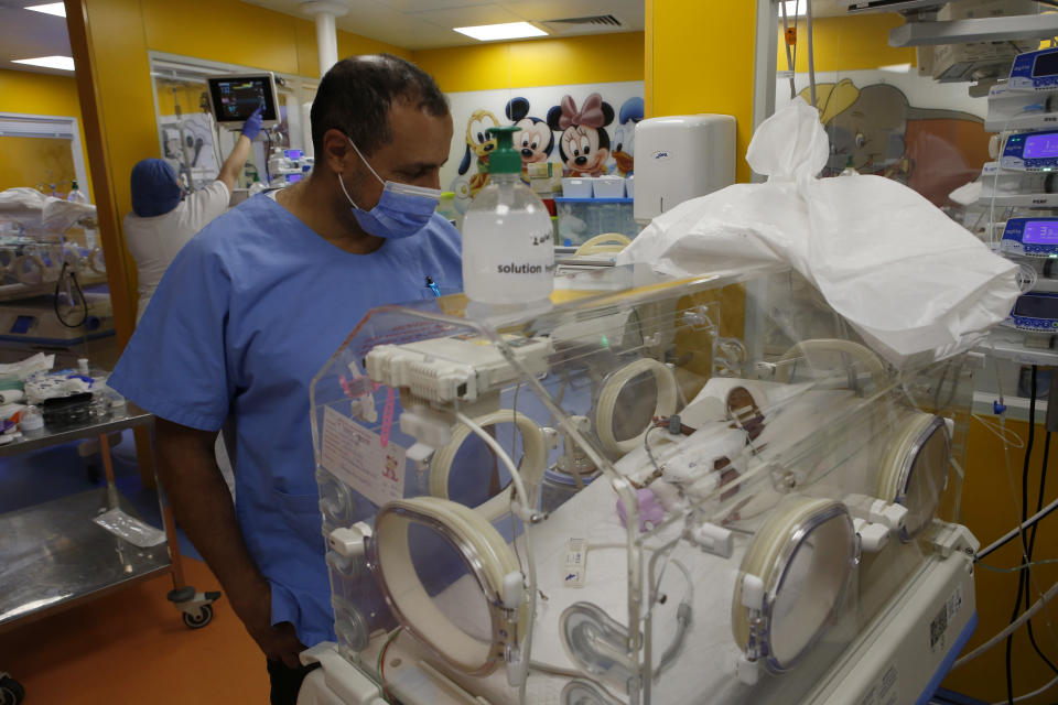 Paediatrician Dr. Msayif Khali watches one of the nine babies protected in an incubator at the maternity unit of the Ain Borja clinic in Casablanca, Morocco, Thursday May 20, 2021, two weeks after Mali's Halima Cisse, 25, gave birth to nine healthy babies. (AP Photo / Abdeljalil Bounhar)