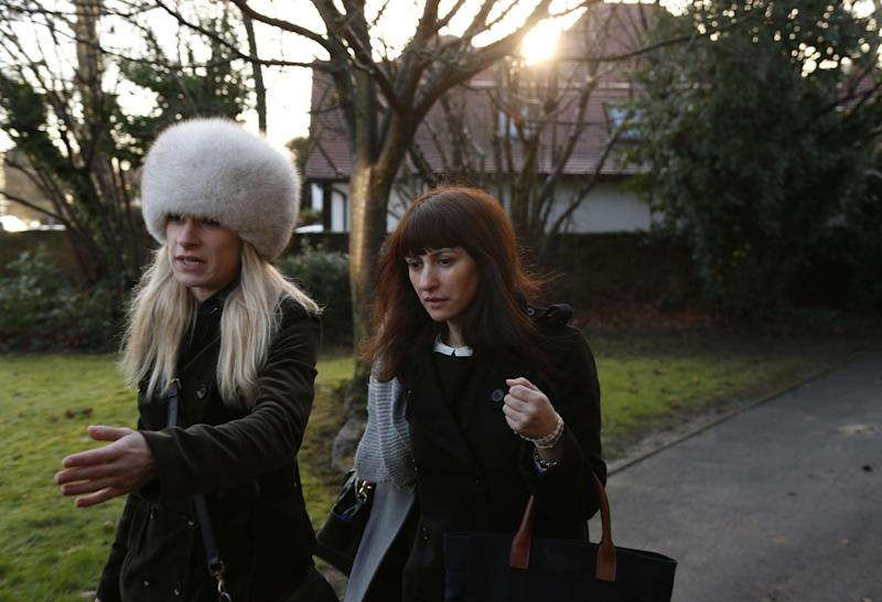 Italian sisters Francesca, centre, and Elisabetta Grillo, obscured behind her, former personal assistants of English broadcaster Nigella Lawson and her former husband art collector Charles Saatchi, arrive at the Isleworth Crown Court, in west London, Friday, Dec. 20, 2013, during a trial over alleged fraud. Grillos are accused of committing fraud by abusing their positions as PAs by using a company credit card for personal gain between Jan. 1, 2008 and Dec. 31, 2012. (AP Photo/Lefteris Pitarakis)