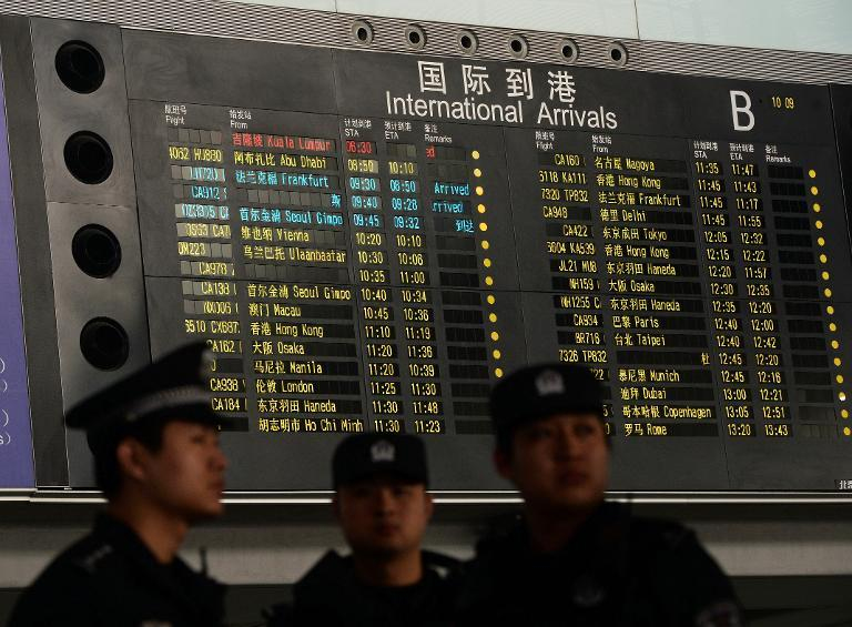 Chinese police stand beside the arrival board showing the flight MH370 (top-red) at the Beijing Airport after news of the Malaysia Airlines Boeing 777-200 plane disapeared on March 8, 2014