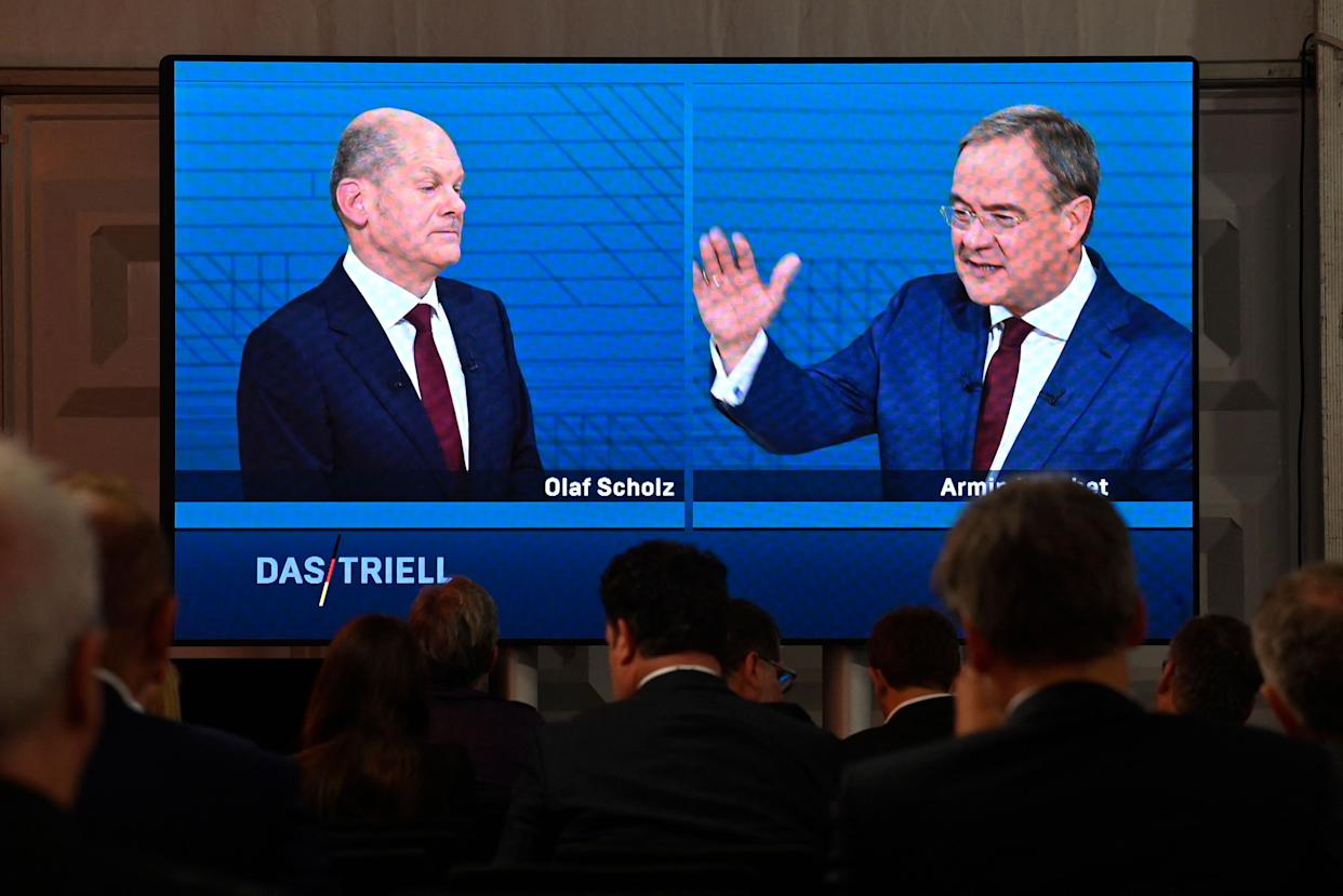 Journalists and party members watch on a screen from the press centre (L-R) Olaf Scholz, German Finance Minister, Vice-Chancellor and the Social Democrats (SPD) candidate for Chancellor and Armin Laschet, North Rhine-Westphalia's State Premier and the Christian Democratic Union (CDU) candidate for Chancellor as they attend an election TV debate in Berlin on September 12, 2021, ahead of general elections taking place on September 26, 2021. (Photo by John MACDOUGALL / AFP) (Photo by JOHN MACDOUGALL/AFP via Getty Images)