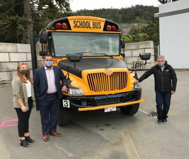 Tracey Syrota, Ravi Parmar and bus driver Al Kowalko stand with one of the Sooke school district's new electric school buses.  (School District 62/Twitter - image credit)