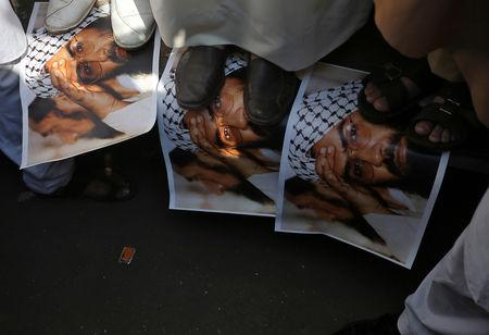 Demonstrators step on the posters of Maulana Masood Azhar, head of Pakistan-based militant group Jaish-e-Mohammad, during a protest in Mumbai