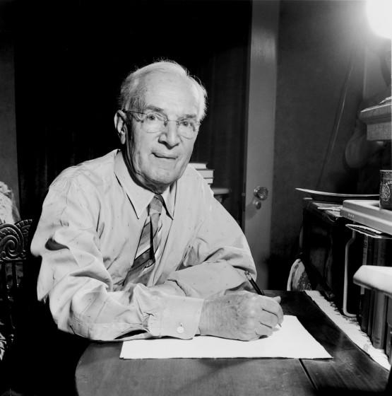 """American author Upton Sinclair, writing by the light of his desk at home in California in 1948. His campaigns for California governor nurtured a strain of progressivism that has persisted in the state for more than a century. <span class=""""copyright"""">(Murray Garrett / Getty Images)</span>"""