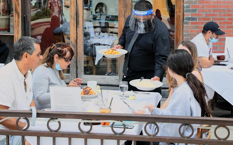 A waiter wears a protective face shield at a Third Street Promenade restaurant. - Getty