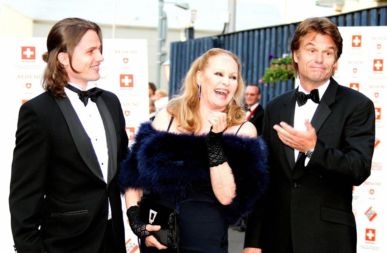Edinburgh, UNITED KINGDOM:  Swiss Hollywood film star Ursula Andress (C) arrives with her son Dimitri Hamlin (L) and former partner Harry Hamlin at The Royal Yacht Britannia in Edinburgh, Scotland, 18th May 2006, to take part in a special party to celebrate her 70th birthday. Andress was the original 'Bond Girl' having become famous for her role as Honey Rider in the James Bond film, Dr. No.  AFP PHOTO/GORDON JACK  (Photo credit should read GORDON JACK/AFP via Getty Images)