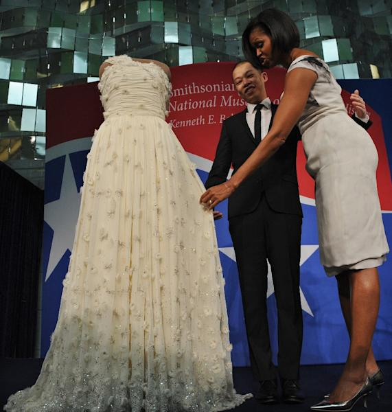 US First Lady Michelle Obama looks at her 2009 inaugural gown as the designer of Mrs. Obama's dress, Jason Wu stands by, during a ceremony at the Smithsonian's National Museum of American History in Washington, DC, in 2010 (AFP Photo/JEWEL SAMAD)