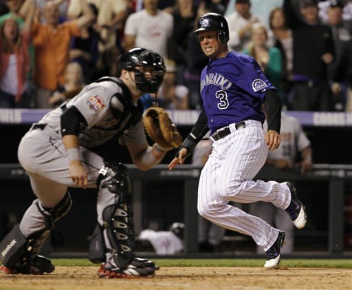 Colorado Rockies' Michael Cuddyer, right, slides safely into home plate to score the winning run as Houston Astros catcher Chris Snyder waits for the throw in the 10th inning of the Rockies' 7-6 victory in in game two of a split doubleheader in Denver on Monday, May 28, 2012. Cuddyer scored from first base on a single by Dexter Fowler. (AP Photo/David Zalubowski)
