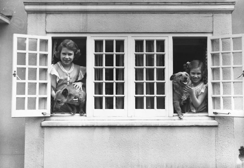 Queen Elizabeth II and Princess Margaret at the windows of Y Bwthyn Bach, aka the Welsh House, a miniature house presented to them by the people of Wales, built in the grounds of the Royal Lodge, Windsor, 1936