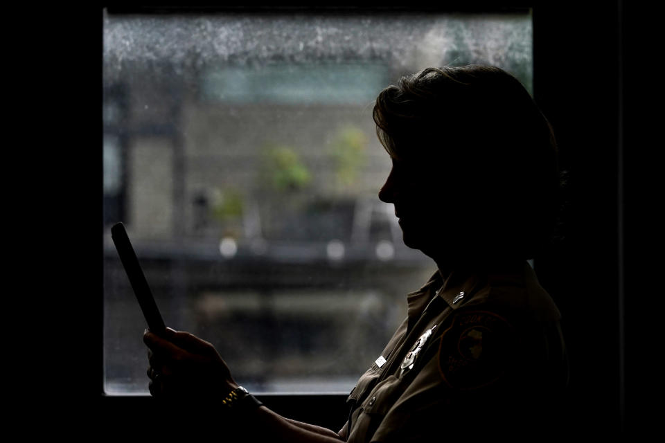 In this Friday, Aug. 13, 2021, photo Sheriff's Police Sgt. Bonnie Busching holds a tablet as she tests a virtual meeting with mental health professional at the Cook County Sheriff's Office in Chicago. The Cook County Sheriff's department officers are hitting the streets with tablets that can connect people in distress immediately with mental health professionals. And Cook County Sheriff Tom Dart says the Treatment Response Team has been successful bringing calm to the tensest of domestic situations involving people at risk of hurting themselves or others. (AP Photo/Nam Y. Huh)