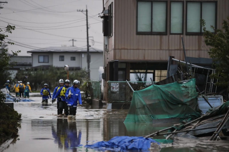 Search and rescue team members wade through floodwaters Monday, Oct. 14, 2019, in Hoyasu, Japan. Rescue crews in Japan dug through mudslides and searched near swollen rivers Monday as they looked for those missing from a typhoon that left as many as 36 dead and caused serious damage in central and northern Japan. (AP Photo/Jae C. Hong)