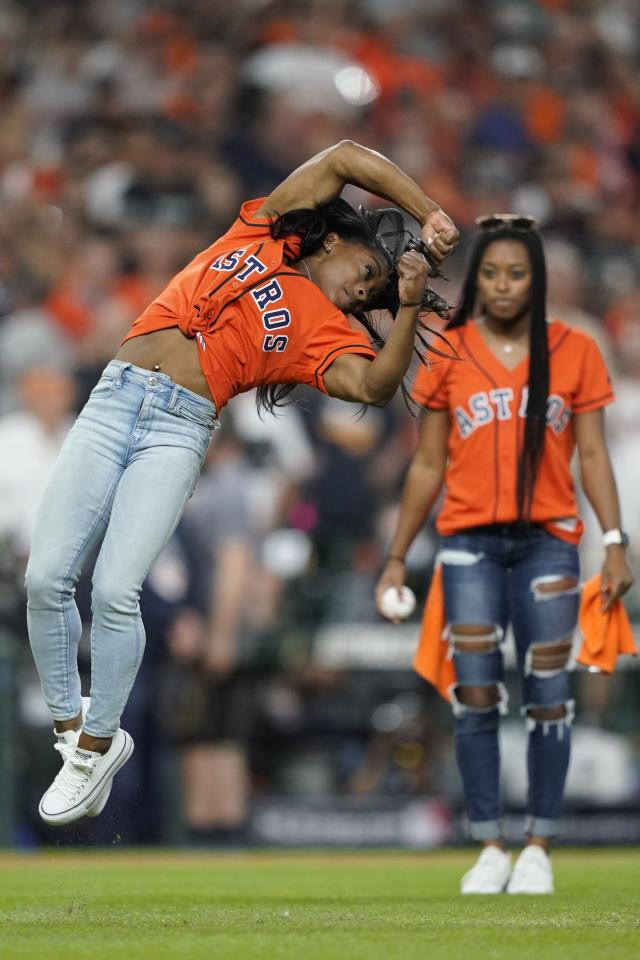 Gymnast Simone Biles does a flip before throwing the ceremonial first pitch before Game 2 of the baseball World Series between the Houston Astros and the Washington Nationals Wednesday, Oct. 23, 2019, in Houston. (AP Photo/David J. Phillip)