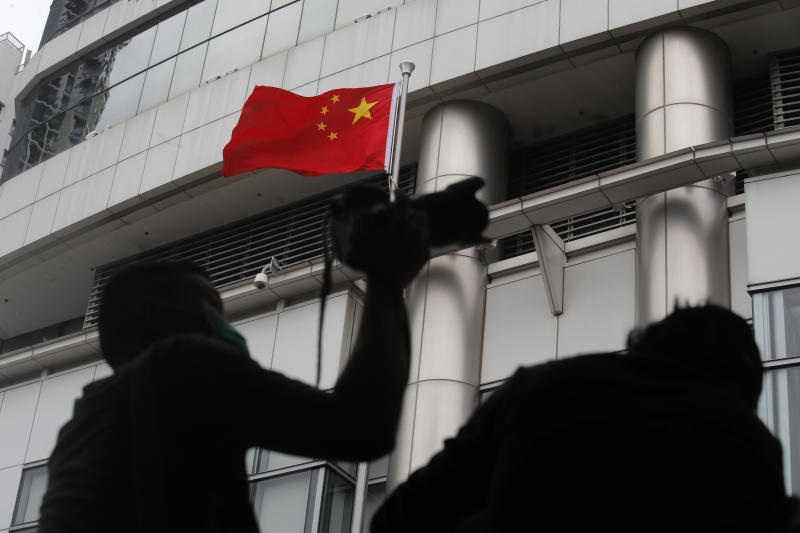 Journalists take picture and video over the water-filled barriers after an opening ceremony for China's new Office for Safeguarding National Security in Hong Kong, Wednesday, July 8, 2020. China's new national security office in Hong Kong got off to an early start on Wednesday with an official opening amidst heavy police presence. (AP Photo/Kin Cheung)