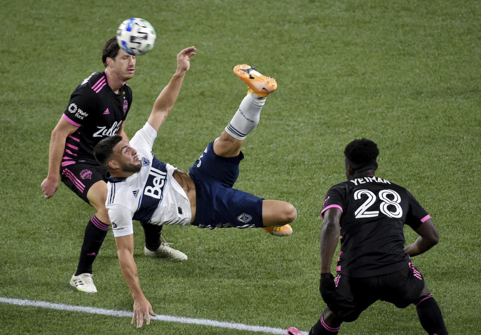 Vancouver Whitecaps forward Lucas Cavallini, center, does a bicycle kick in front of Seattle Sounders defender Yeimar Gomez, right during the second half of an MLS soccer match in Portland, Ore., Tuesday, Oct. 27, 2020. Seattle won 2-0. (AP Photo/Steve Dykes)