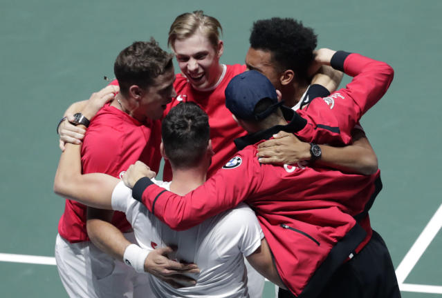 Canada's Vasek Pospisil, left, and his partner Denis Shapovalov, second left, celebrate with team captain Frank Dancevic and teammates after winning their Davis Cup semifinal doubles match against Russia's Karen Khachanov and Andrey Rublev, in Madrid, Spain, Saturday, Nov. 23, 2019. (AP Photo/Bernat Armangue)