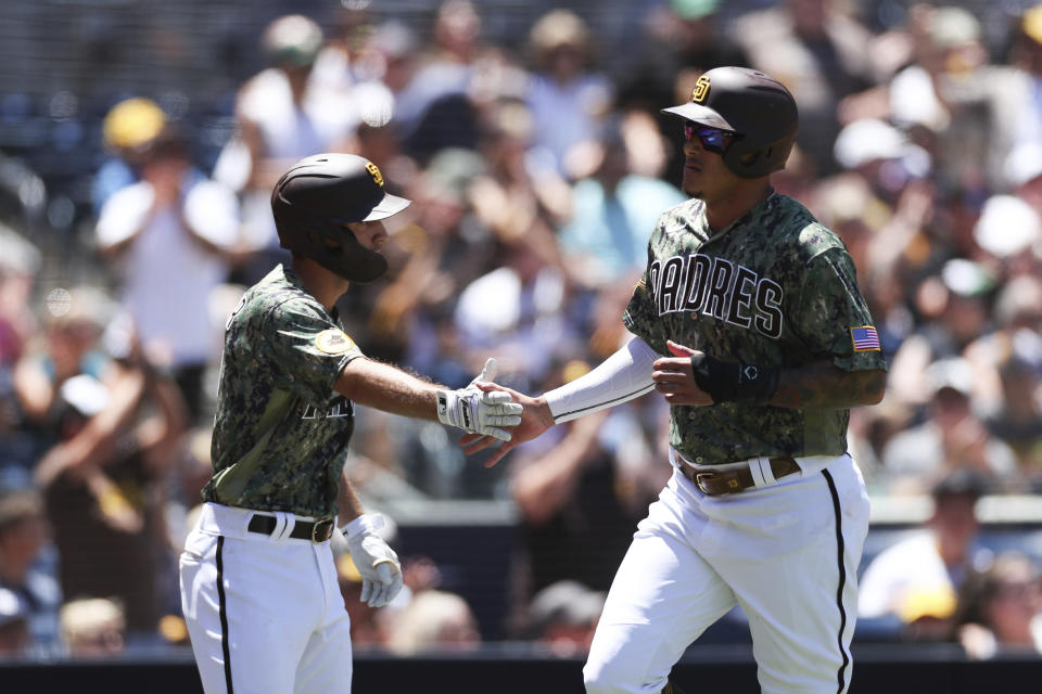 San Diego Padres' Manny Machado, right, celebrates with Adam Frazier after scoring on a double by Jake Cronenworth against the Colorado Rockies, in the first inning of a baseball game Sunday, Aug. 1, 2021, in San Diego. (AP Photo/Derrick Tuskan)