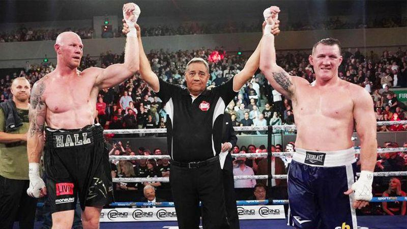 Pictured here, the arms of Barry Hall and Paul Gallen are both held aloft after their draw in the boxing ring.