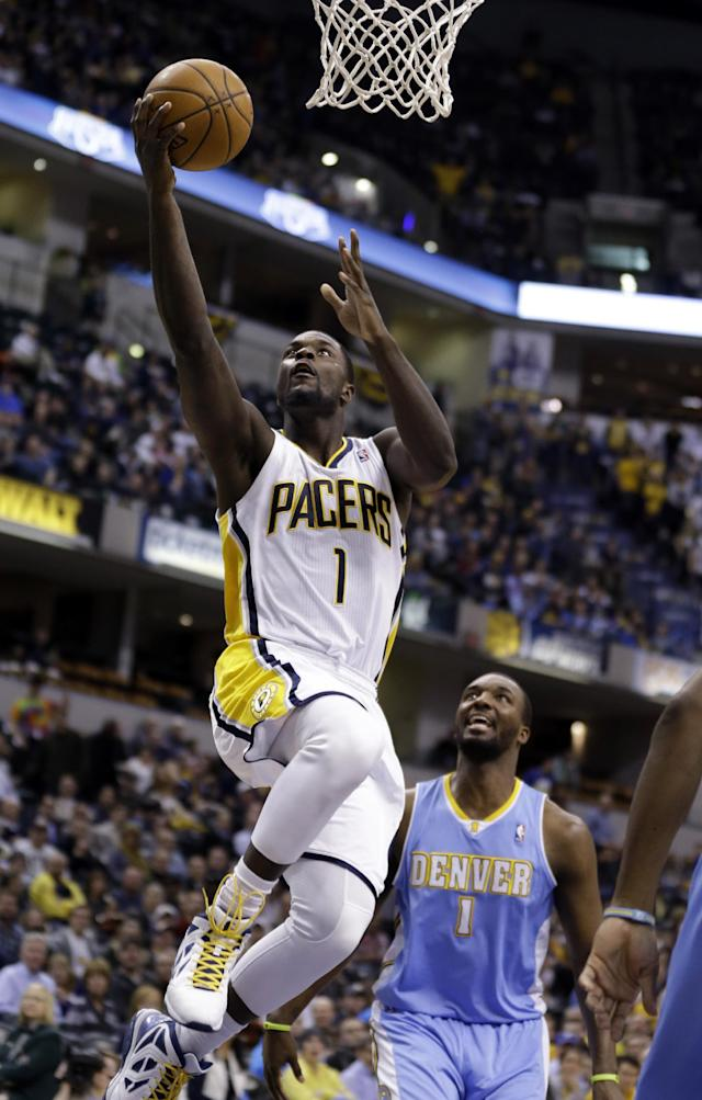 Indiana Pacers guard Lance Stephenson, left, gets a basket in front of Denver Nuggets forward Jordan Hamilton in the second half of an NBA basketball game in Indianapolis, Monday, Feb. 10, 2014. The Pacers won 119-80. (AP Photo/Michael Conroy)