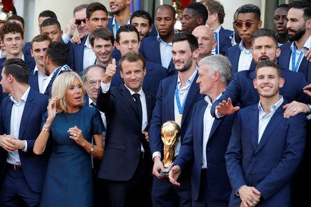French President Emmanuel Macron and his wife Brigitte Macron pose with France soccer team captain Hugo Lloris holding the trophy, coach Didier Deschamps and players before a reception to honour the France soccer team after their victory in the 2018 Russia Soccer World Cup, at the Elysee Palace in Paris, France, July 16, 2018.   REUTERS/Philippe Wojazer