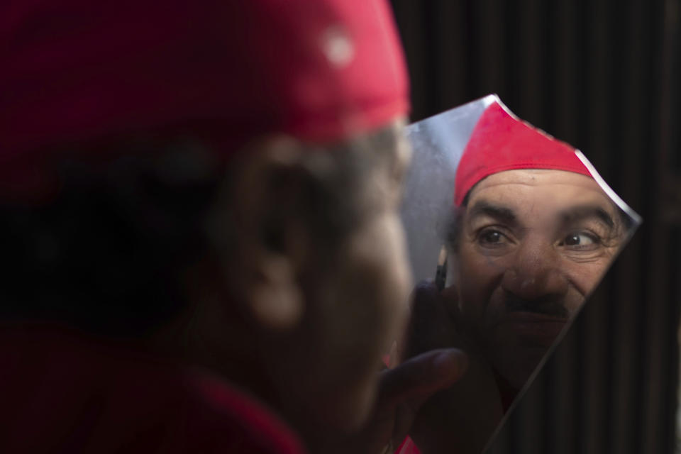 Belhussein Abdelsalam, a Charlie Chaplin impersonator applies makeup as he prepares to start a new day of work, in Rabat, Morocco, Thursday, Dec. 31, 2020. When 58-year-old Moroccan Belhussein Abdelsalam was arrested and lost his job three decades ago, he saw Charlie Chaplin on television and in that moment decided upon a new career: impersonating the British actor and silent movie maker remembered for his Little Tramp character. the television and decided in that moment upon a new career: Impersonating the American Silent Movie star. (AP Photo/Mosa'ab Elshamy)