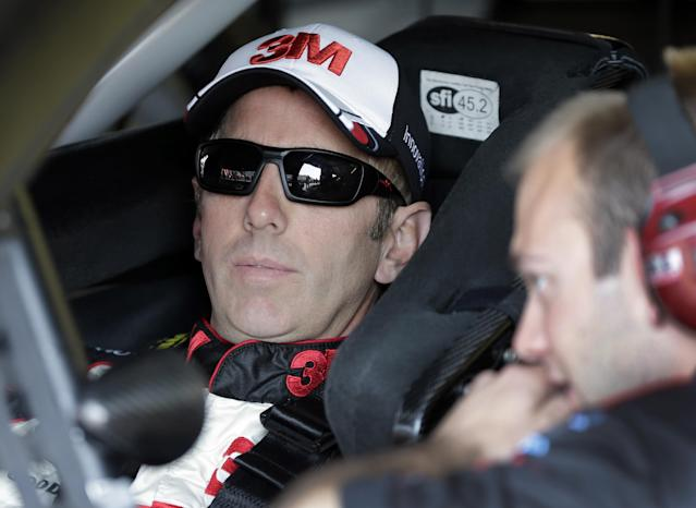 Greg Biffle, left, talks to a crew member before a NASCAR Sprint Cup series auto race practice at Darlington Speedway in Darlington, S.C., Friday, April 11, 2014. (AP Photo/Chuck Burton)