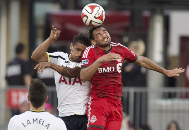 Tottenham Hotspur's Kyle Naughton, center, and Toronto FC's Gilberto Oliveira Souza Junior battle for the ball during the first half of a friendly soccer match in Toronto on Wednesday, July 23, 2014. (AP Photo/The Canadian Press, Darren Calabrese)