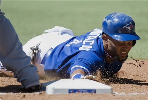 Toronto Blue Jays centre fielder Emilio Bonifacio slides back to first base safe as Seattle Mariners first baseman Justin Smoak is late with the tag during second inning MLB American League baseball action in Toronto on Sunday, May 5, 2013. (AP Photo/THE CANADIAN PRESS,Nathan Denette)