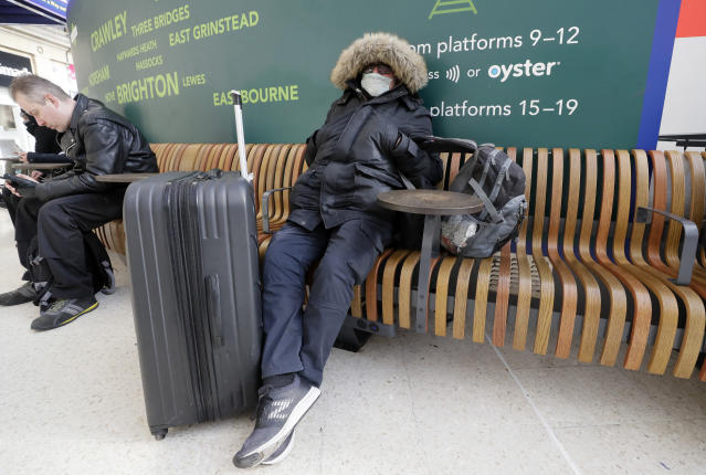 A traveller wears a mask as he waits at Victoria Station in London (AP)