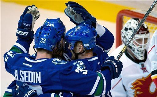 Vancouver Canucks' Henrik Sedin, of Sweden, from left, Alex Burrows and Daniel Sedin, of Sweden, celebrate Burrows' goal in front of Calgary Flames' goalie Miikka Kiprusoff, of Finland, during the second period of an NHL hockey game in Vancouver, British Columbia, on Saturday April 6, 2013. (AP Photo/The Canadian Press, Darryl Dyck)
