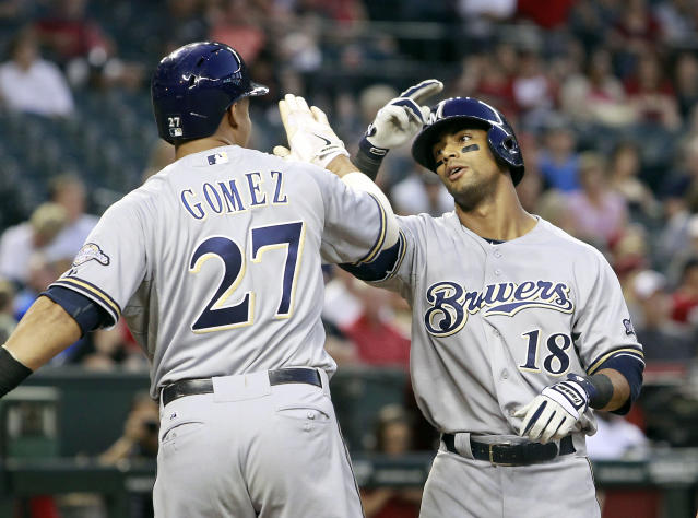 Milwaukee Brewers' Khris Davis (18) is congratulated after crossing home plate by teammate Carlos Gomez (27) following his three-run home run against the Arizona Diamondbacks during the fourth inning of a baseball game on Wednesday, June 18, 2014, in Phoenix. (AP Photo/Ralph Freso)