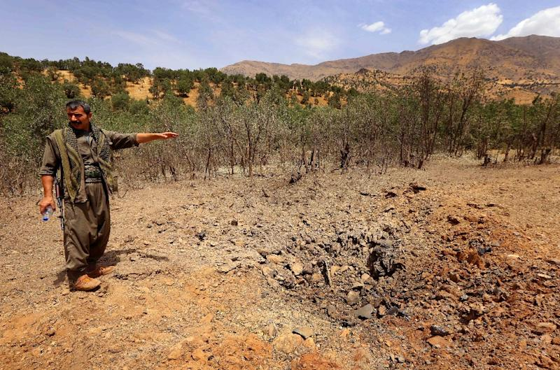 A member of the Kurdistan Workers' Party (PKK) inspects a crater reportedly caused by an air strike from Turkish warplanes on July 29, 2015 in the Qandil mountain (AFP Photo/Safin Hamed)