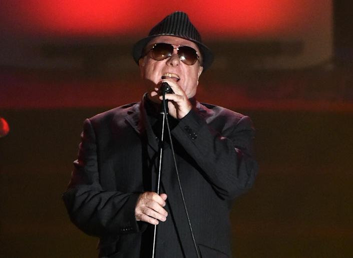 Van Morrison, wearing sunglasses and a hat, sings into a microphone.