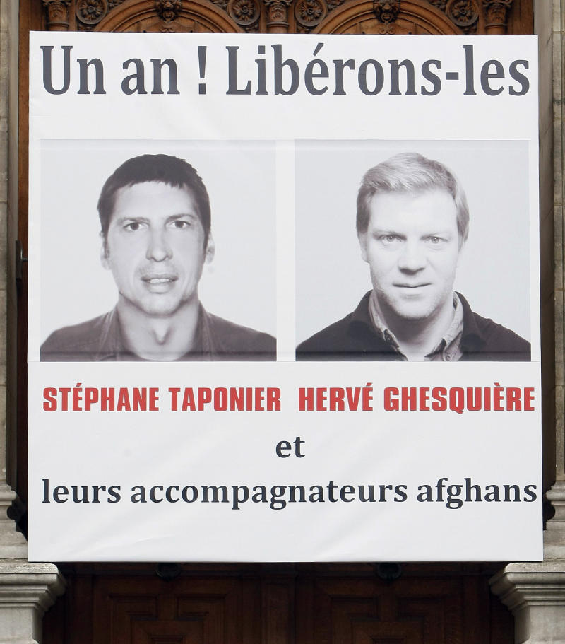 "FILE - A Dec. 29, 2010 file photo of a banner on Paris city hall showing  French TV journalists Herve Ghesquiere, right, and Stephane Taponier, who were kidnapped a year ago east of Kabul, Afghanistan, in front of Paris city hall. The banner in back, reads: ""One year! Let us free them and their Afghan fixers"". The French government announced Wednesday June 29 2011, that the two hostages have been freed after being held 547 days. (AP Photo/Remy de la Mauviniere, file)"