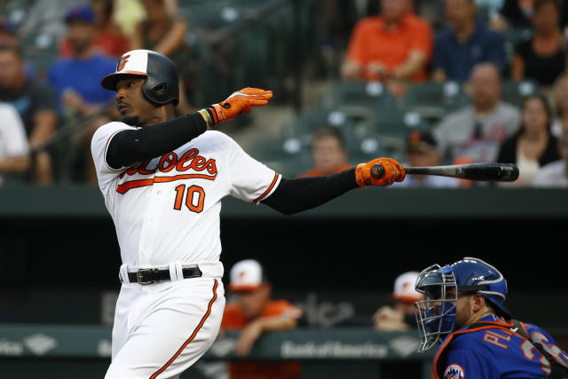 Baltimore Orioles' Adam Jones follows through on an RBI single in front of New York Mets catcher Kevin Plawecki during the first inning of a baseball game Wednesday, Aug. 15, 2018, in Baltimore. (AP Photo/Patrick Semansky)