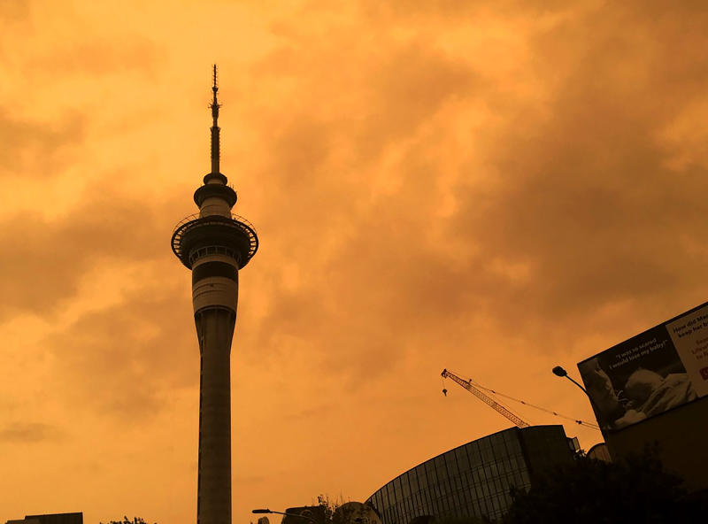 The sky above Auckland's Sky Tower turns orange as smoke from the Australia wildfires arrives in New Zealand, Sunday, Jan. 5, 2020. Australian Prime Minister Scott Morrison defended his leadership and his government's record on climate change Sunday as milder temperatures brought hope of a respite from wildfires that have ravaged three states, destroying almost 2,000 homes. (Luke Kirkness/New Zealand Herald via AP)