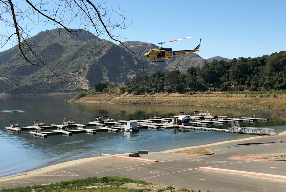 """A Ventura County Sheriff's helicopter aids in the search on Thursday, July 9, 2020, for """"Glee"""" actress Naya Rivera, who was missing after renting a boat with her 4-year-old son at Lake Piru on Wednesday."""